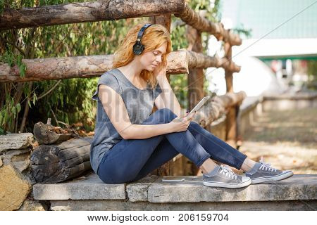 Cute pretty girl sitting on the bench with black headphone in the park. Full lenght of blonde girl.