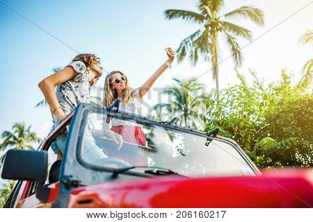 group of three russian tourists taking selfie on off road truck in koh samui thailand shot with lens flare