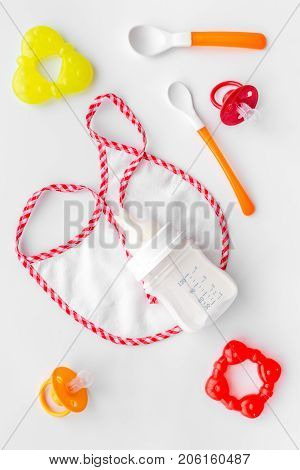 bottle with breastmilk and infant formula powdered healthy food, toys and bib on white desk background top view