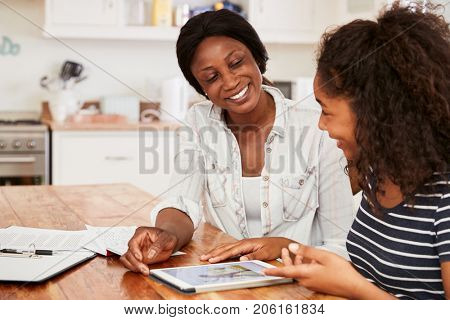 Mother Helps Teenage Daughter With Homework Using Digital Tablet