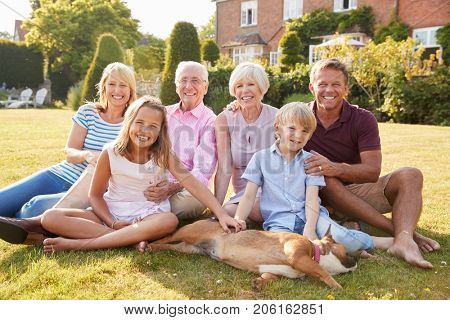 Multi generation family sitting on grass in the garden
