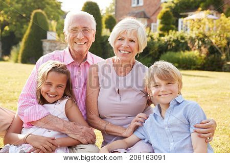 Grandparents and grandchildren sitting on grass in a garden