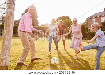 Multi generation family playing football in the garden
