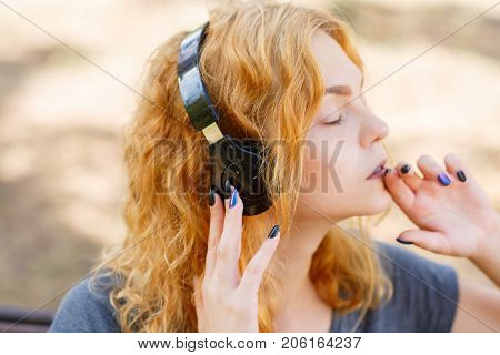 Pretty girl listening music with black headphone in the park. Close-up of blonde girl.