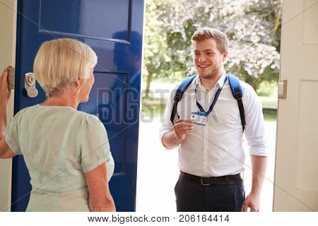Senior woman opens door to male care worker showing his ID