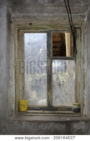 old and dirty window with an irradiated paint and a dirty yellow mug on the windowsill