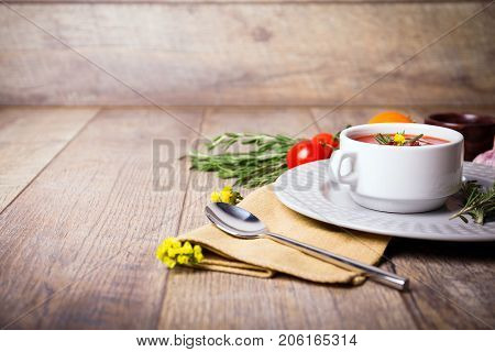 Red ukrainian borsch with sour, garlic, parsley, spices and a lot of dill and parsley on a wooden background. Copy space. Close-up of appetitzing dish. Food concept.