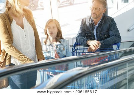 Family going down escalator of shopping mall
