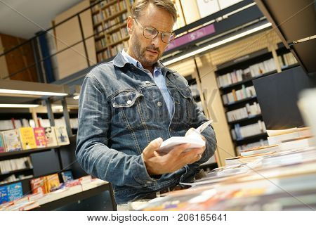 Man in bookstore looking at new books