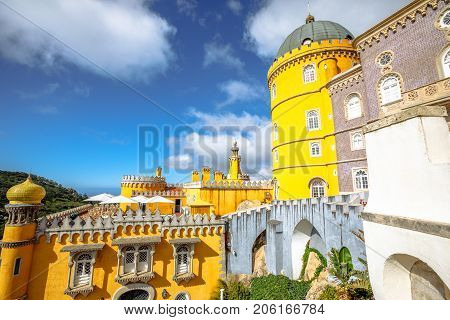 Spectacular view of National Palace of Pena, one of the seven wonders of Portugal with its colors and different architectural styles. Popular landmark of Sintra near Lisbon. Sunny day in the blue sky.