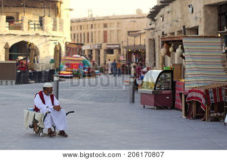 DOHA, Qatar: July 6, 2017: A porter in Souq Waqif sits in his wheelbarrow waiting for business in the popular market. Selective focus, shallow dof,