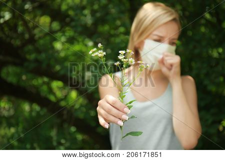 Young woman with allergy holding flower outdoors