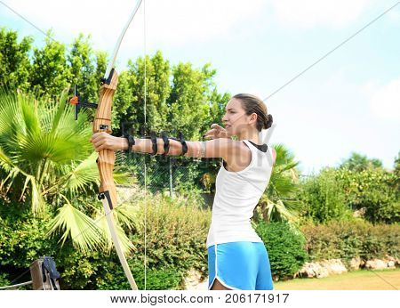 Woman practicing archery on sunny day
