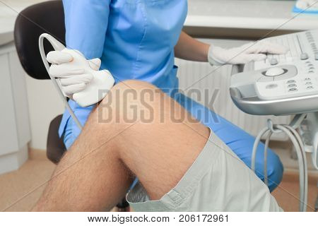 Doctor conducting ultrasound examination of patient's knee in clinic