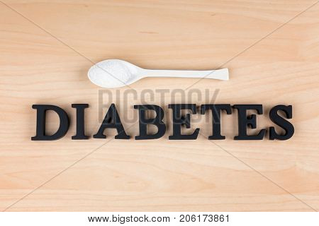 Word Diabetes and sugar in spoon on light background