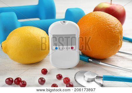 Composition with digital glucometer and fresh fruits on light background. Diabetes concept