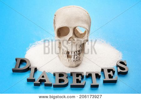 Composition with word Diabetes, sugar and human skull on color background