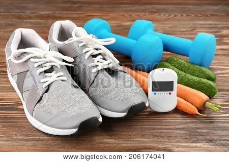 Composition with digital glucometer, vegetables and sport inventory on wooden background. Diabetes concept
