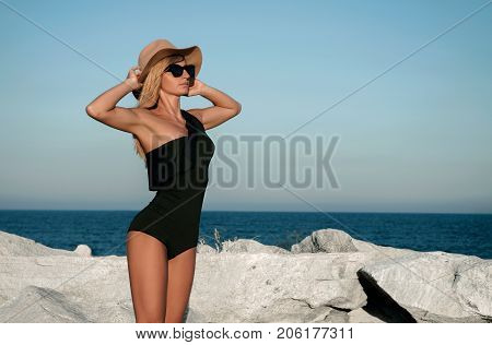 Beautiful Girl  In Black Swimsuit And Hat On The Beach