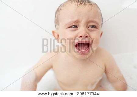 A Crying baby by in a bathtub. Infant kid sreaming while taking a bath.
