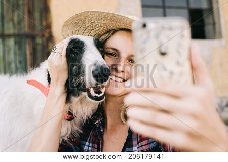 Young woman taking self portrait with her dog