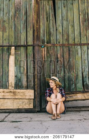Country girl relaxing at barn door.