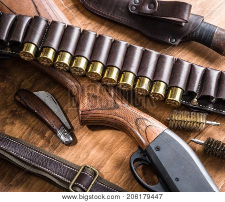 Hunting equipment - pump action shotgun,12 guage cartridge and hunting knife on the wooden table.