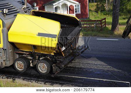 asphalt machine dropping hot asphalt on smaller road
