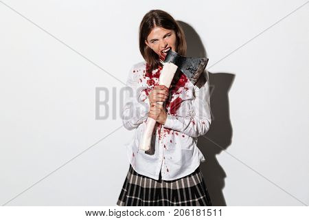 Bleeding scary zombie woman biting an axe isolated over white background