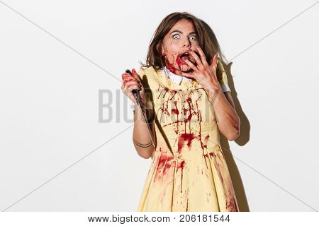 Scared terrified zombie woman covered in blood holding a knife and looking at camera isolated over white background