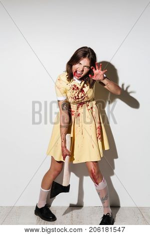 Full length of a mad woman in zombie make up covered with blood stains standing and holding an axe isolated over white background