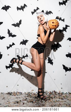 Image of beautiful young woman in halloween costume cat on party over white background with pumpkin. Looking aside.