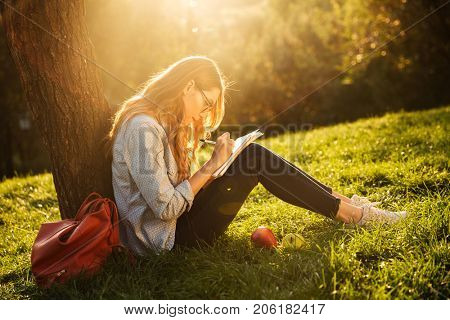 Side view of petty brunette woman sitting near the tree in park and writing something on notebook