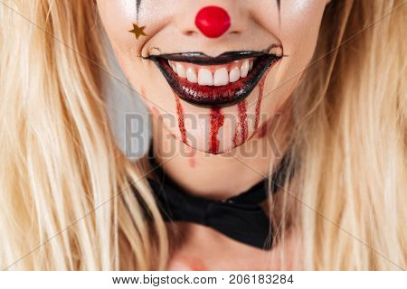 Close up portrait of a smiling blond woman in halloween clown make-up and blood streaks on her face laughing isolated over gray background