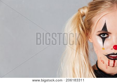 Half face portrait of a young blond woman in halloween clown make-up and blood streaks on her face looking at camera isolated over gray background