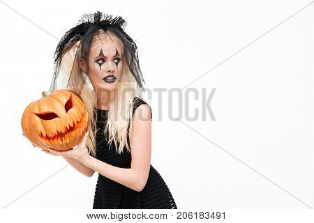 Dreadful blonde woman dressed in black widow costume holding halloween pumpkin and looking away at copy space isolated over white background