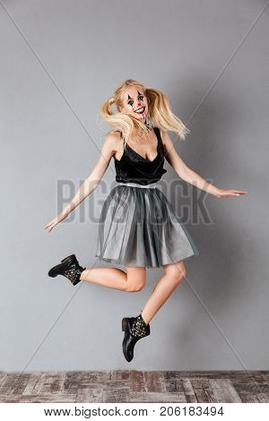 Full length portrait of a cheerful crazy blonde woman in halloween clown make-up and blood streaks jumping and looking at camera isolated over gray background