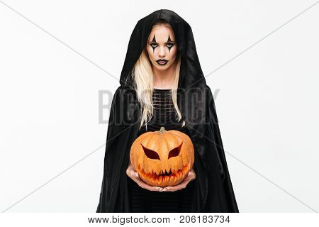 Portrait of a young blonde woman in halloween make-up and black robe holding curved pumpkin isolated over white background