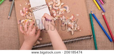 Hand Holding A Color Pencil On Spiral Notebooks