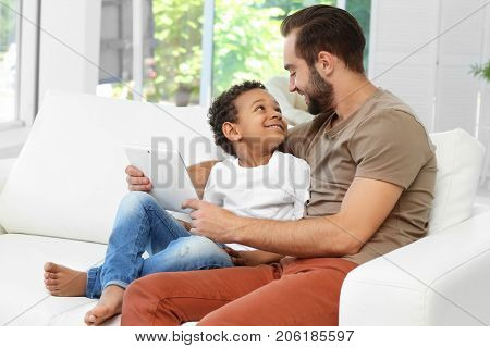 Happy father with adopted African-American boy using tablet computer while sitting on couch at home