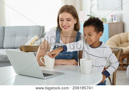 Happy mother with adopted African-American boy using laptop at home