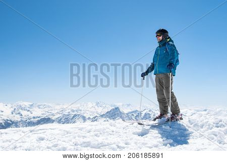Young man ready for skiing on snowy mountain. Sporty guy looking away with ski equipments. Skier in ski clothing preparing for ski with copy space.