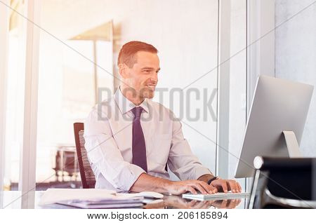 Young office businessman working on desktop computer. Smiling business man typing on keyboard at computer in modern office. Happy man writing an email in his new office.