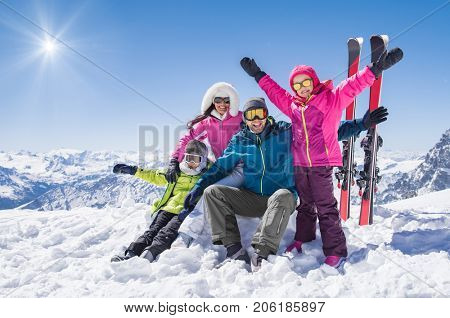 Laughing family in winter vacation with ski sport on snowy mountains. Happy man and woman with sons having fun and looking at camera. Family with two children enjoying winter holiday at ski resort.