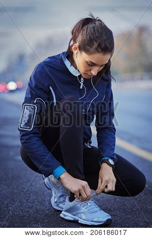 Young woman athlete with earphones listening to music and tying laces on street. Runner tying running shoes while running in the city. Girl preparing for cardio training outdoor at dusk.