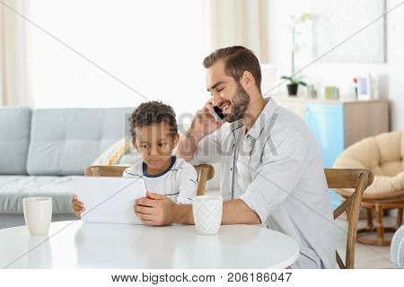 Happy father with adopted African-American boy using tablet computer in living room
