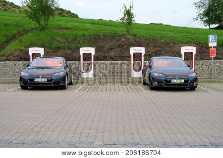 INNSBRUCK AUSTRIA - MAY 18 : Two electric cars recharge at a Tesla Supercharger free charging station on May 18 2016.