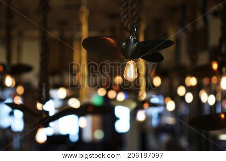 Boat propellers with vintage light bulbs hanging from a ceiling.