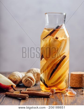 Water infused with Pear Ginger Root and Cinnamon Stick. Some Ingredients on Table. Vertical Orientation and Copy Space.