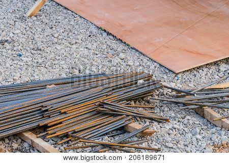 Pile of re-bar laying on the ground covered in small rocks next to a sheet of plywood